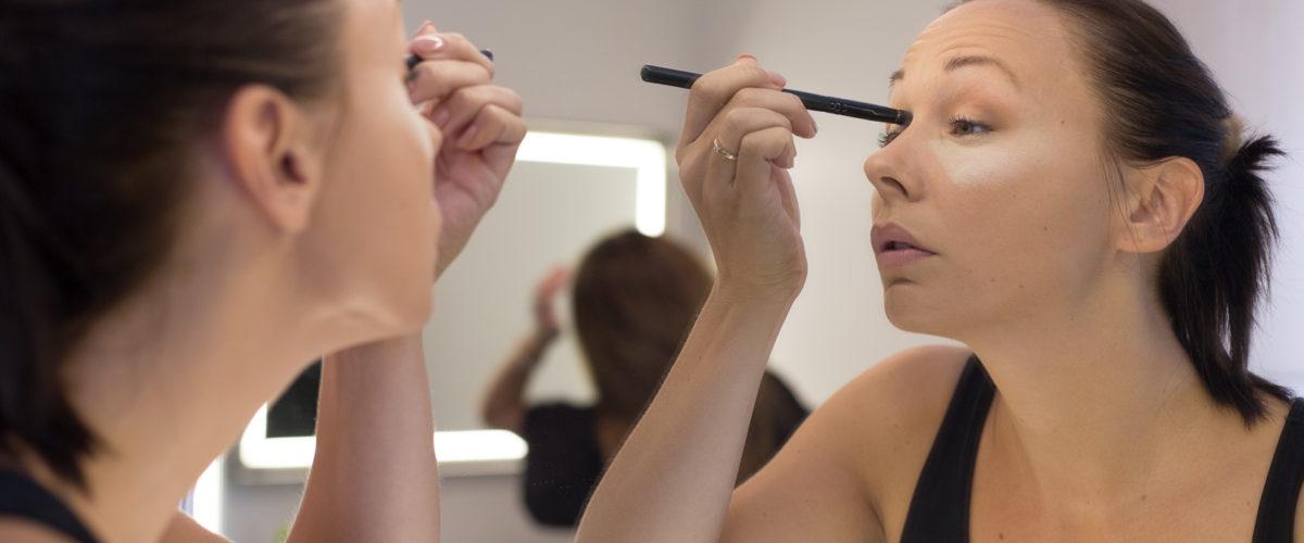 Spejlbillede, der lægges make-up